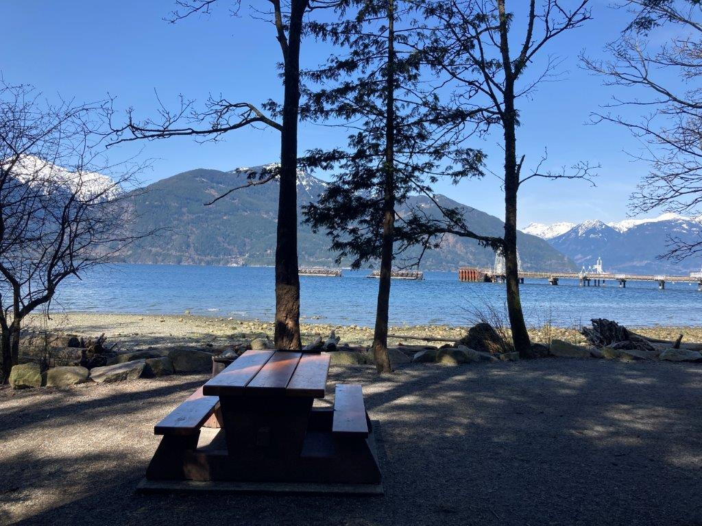 Picnic table and a few trees in front of the ocean and mountains at Porteau Cove Campround - one of the Squamish camping options
