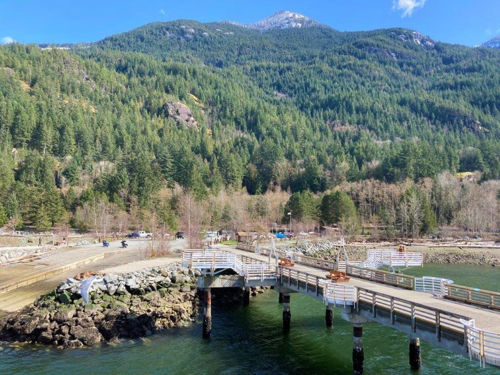 Dock and parking area of the Porteau Cove Provincial Park with trees and a mountain behind