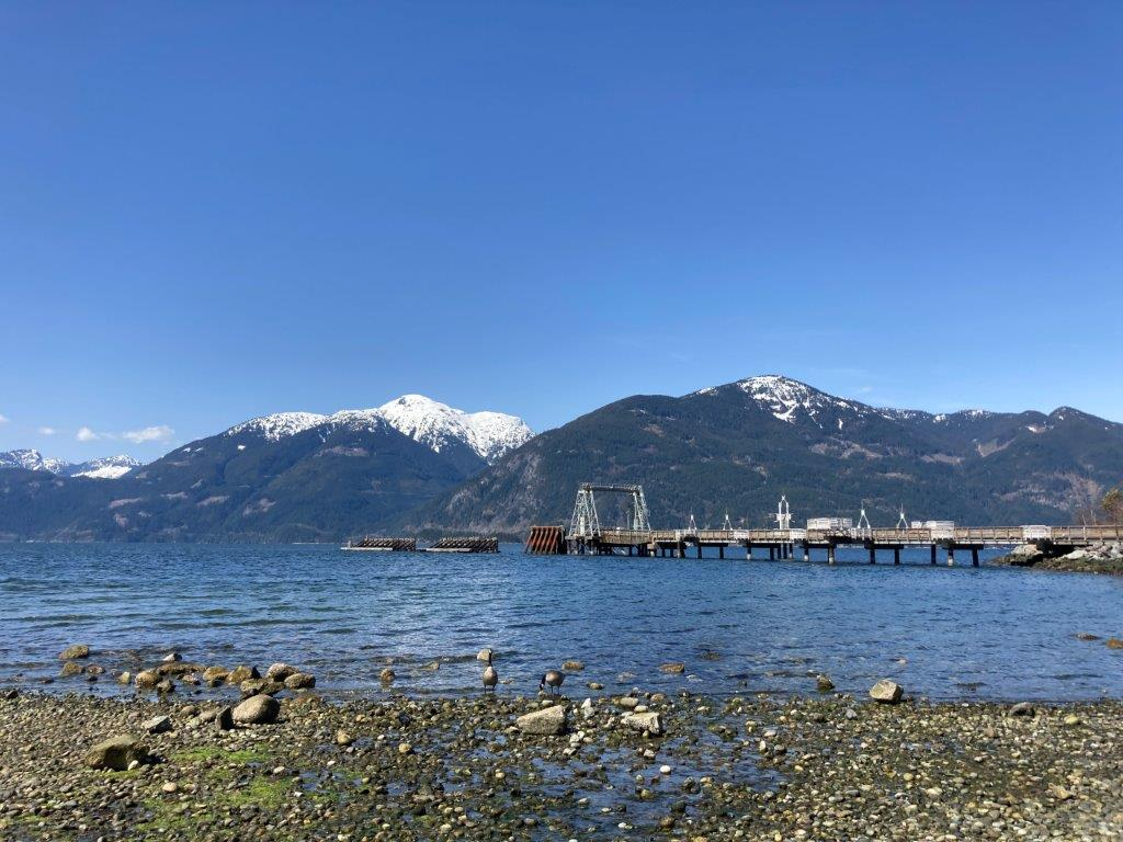 View of the dock and snow covered mountains behind from the beach of Porteau Cove Provinical Park in front of the Porteau Cove Campground