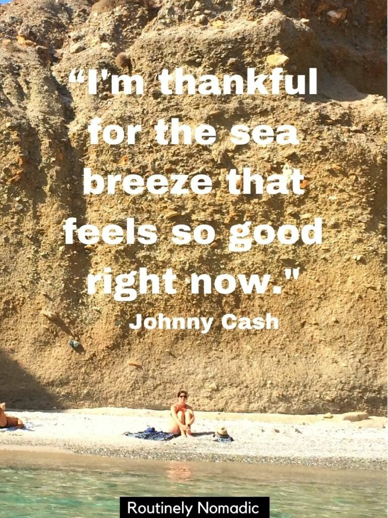Woman sitting on the beach with a cliff behind and the sea in front with a sea breeze quote by Johnny Cash
