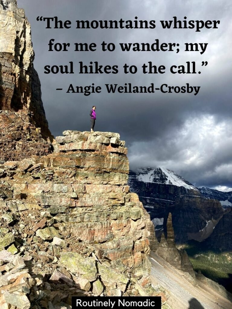 Woman standing on rocky point with mountains and the short mountain quotes that reads the mountains whisper for me to wander, my soul hikes to the call