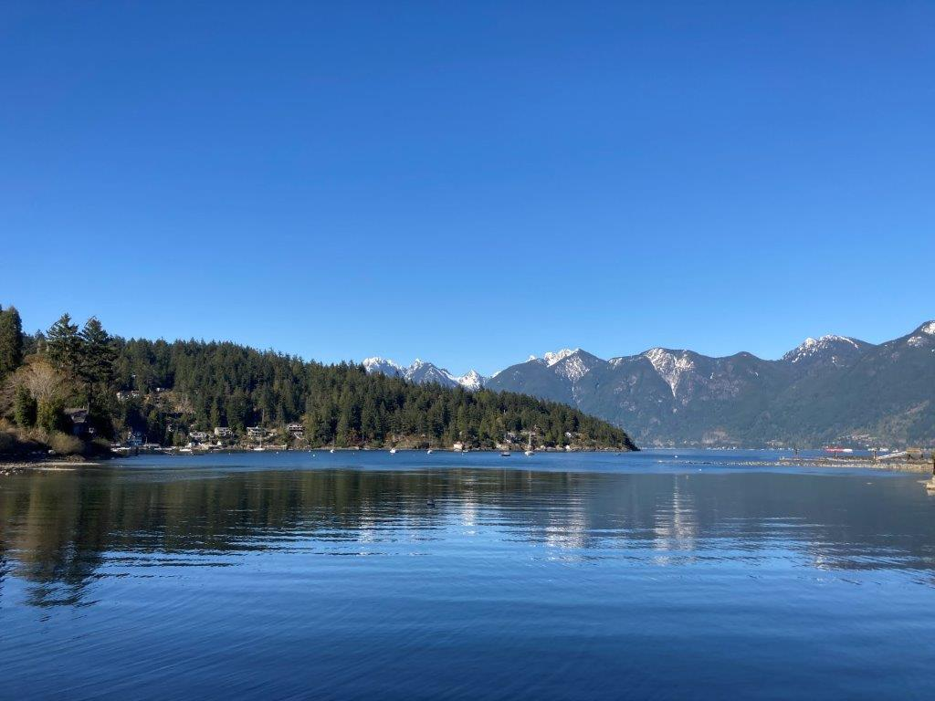 View of the ocean, and snow topped mountains of mainland BC from a Snug Cove Bowen Island beach