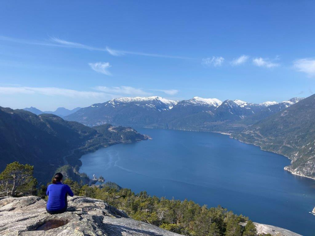 Woman sitting on the Stawamus Chief Mountain First Peak enjoying the view of the Howe Sound with snow covered mountains in the background on The Chief hike