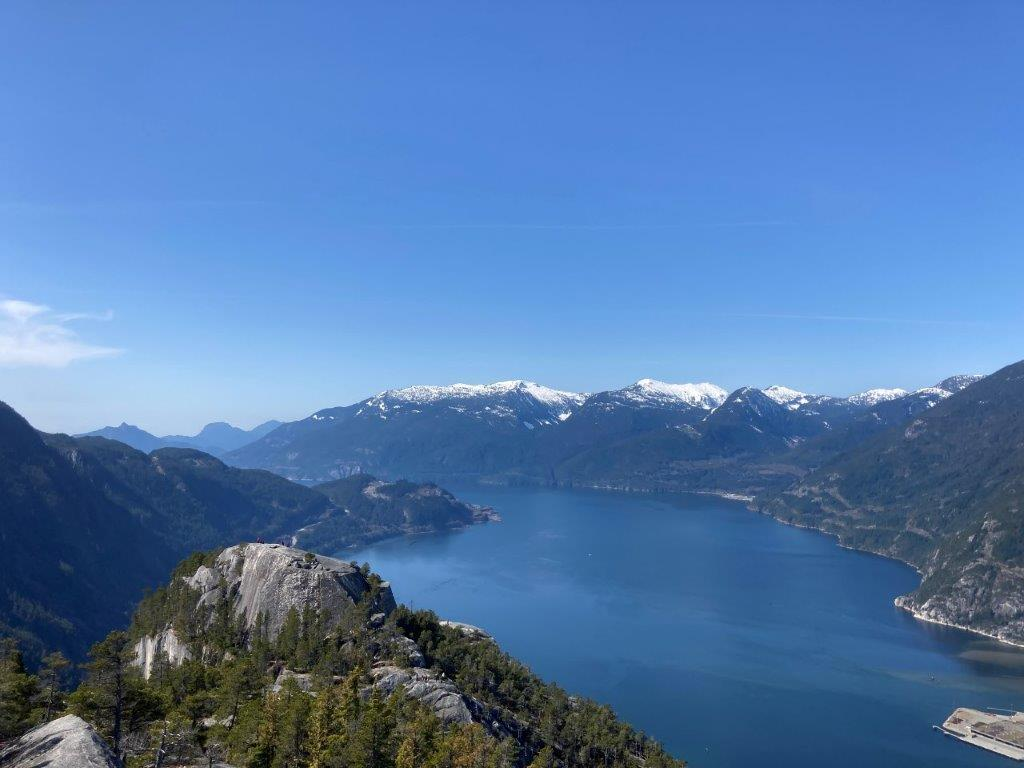 The blue water of the Howe Sound framed with snowy mountains and the first peak of the Chief hike in front