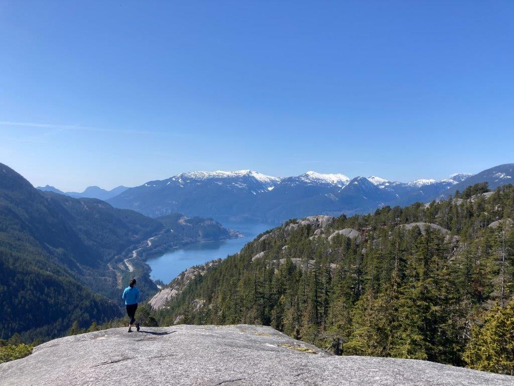 Woman standing on the third peak of the Stawamus Chief Hike looking at the sea to sky highway, the howe sound and snowy mountains