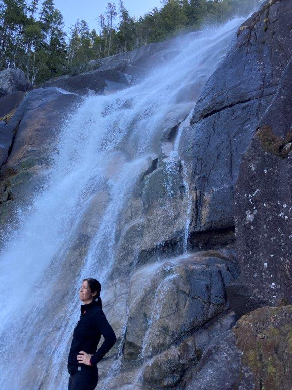 Woman standing in front of the Upper Shannon falls on a Squamish trails