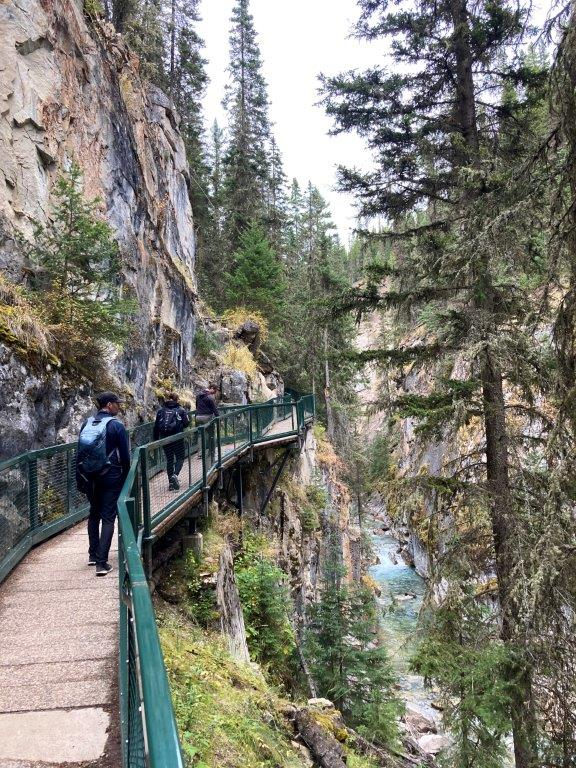 People on the Walkway with railings on a narrow part of the Johnston Canyon hike with a river below and rock walls