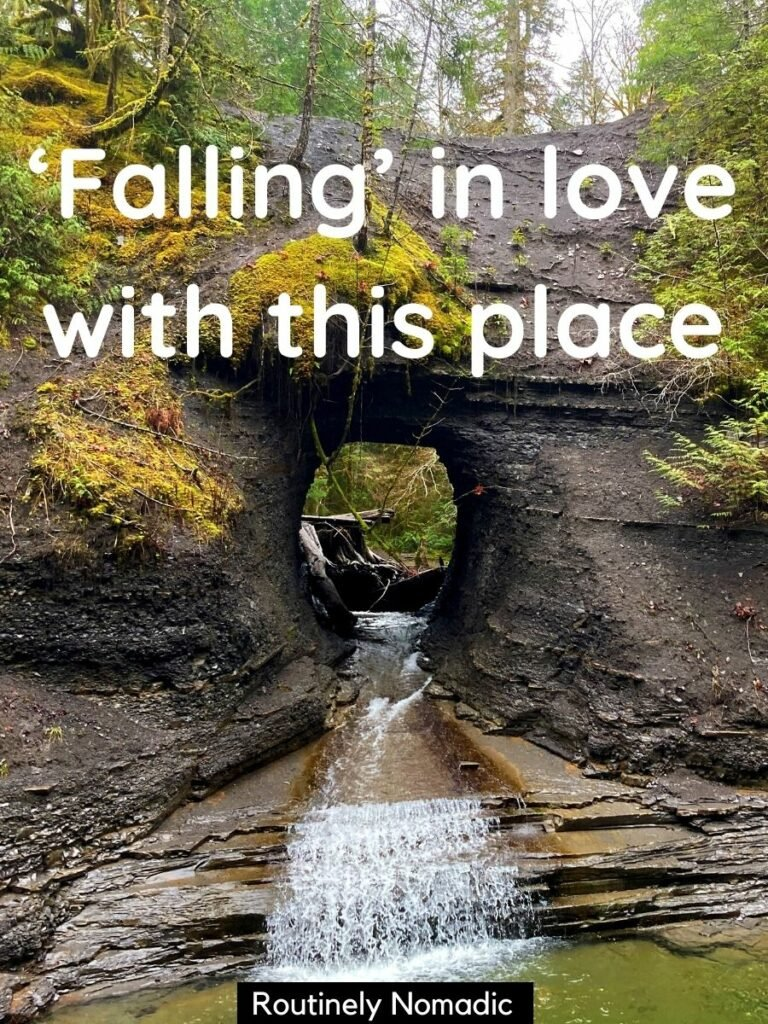A waterfall coming through a round hole in the rock wall with a funny waterfall captions that reads falling in love with this place