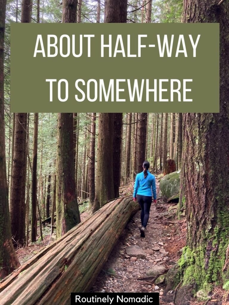 Woman walking beside a fallen tree between tall trees with a funny hiking captions for Instagram that says about half-way to somewhere