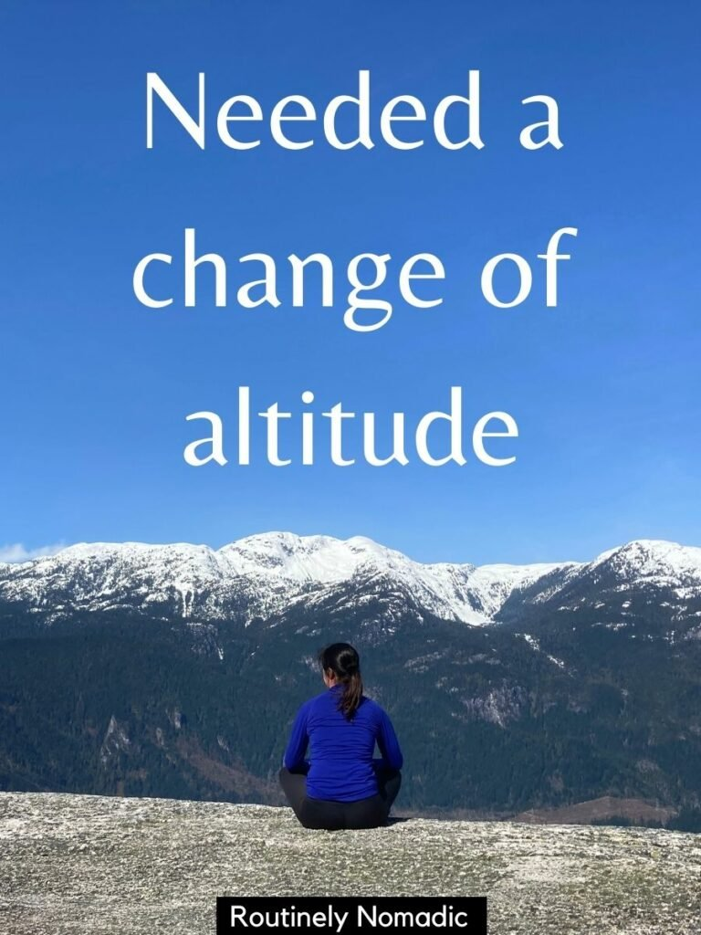 Woman sitting on rocky ledge looking towards snow covered mountains with a funny hiking captions for Instagram that reads - needed a change of attitude