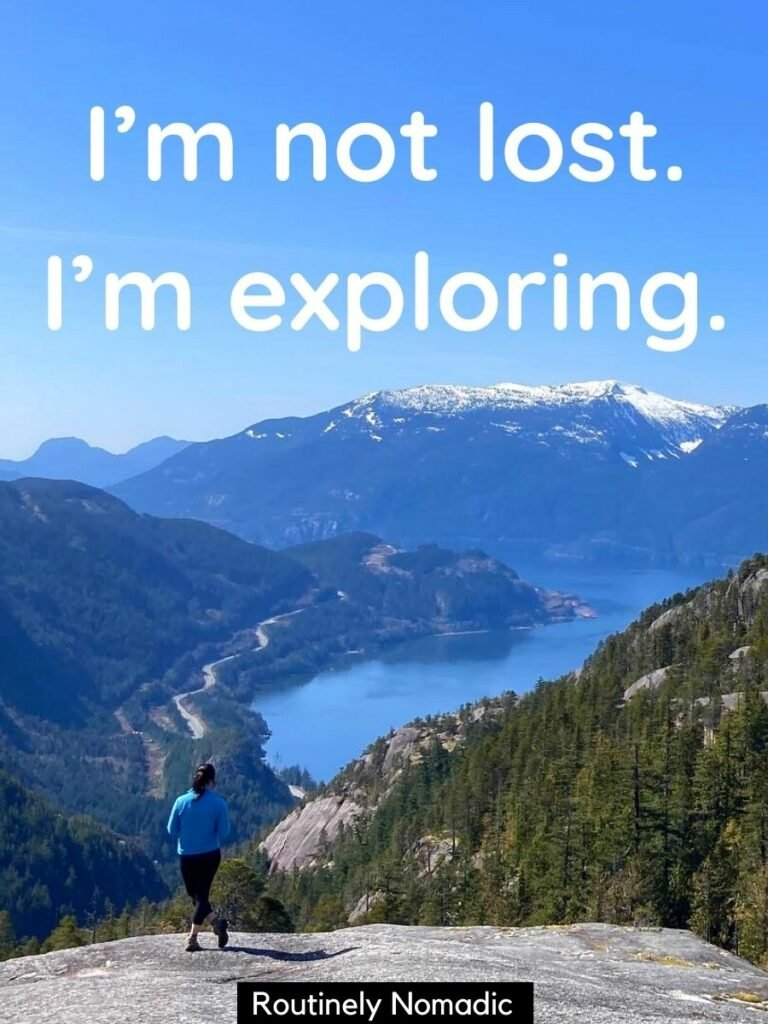 Woman on rocky outcropping looking over water and mountains and a funny hiking captions for Instagram that reads I'm not lost, I'm exploring