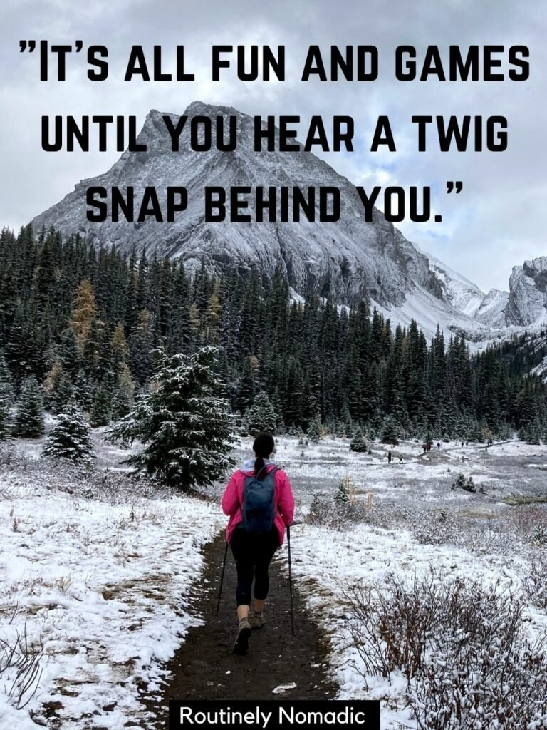 A woman walking along a snowy trail with a mountain in front and a funny hiking quotes that reads it's all fun and games until you hear a twig snap behind you