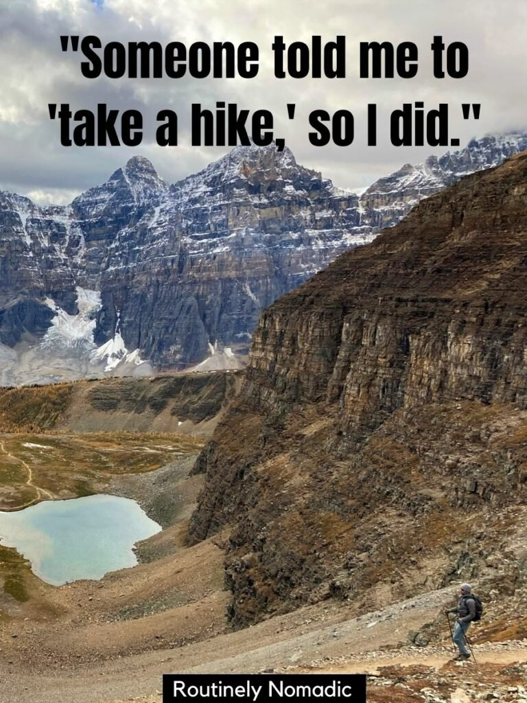 Person hiking with a lake and mountains behind and a funny hiking sayings that says someone told me to take a hike so I did