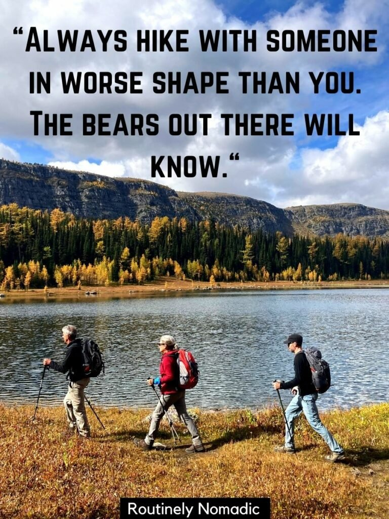 Three people hiking in front of a lake with a funny hiking quote that reads always hike with someone in worse shape than you, the bears out there will know.