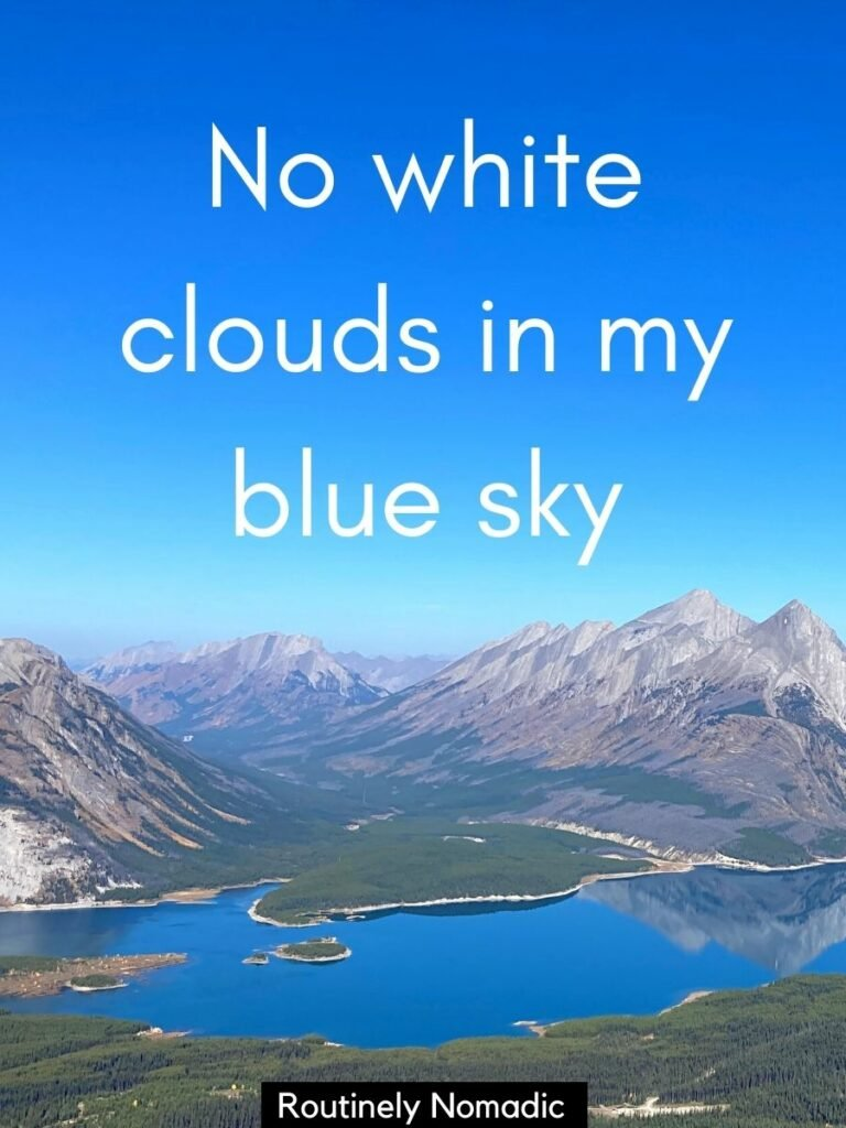 Mountains reflected in a lake with a caption for blue sky that reads no white clouds in my blue sky