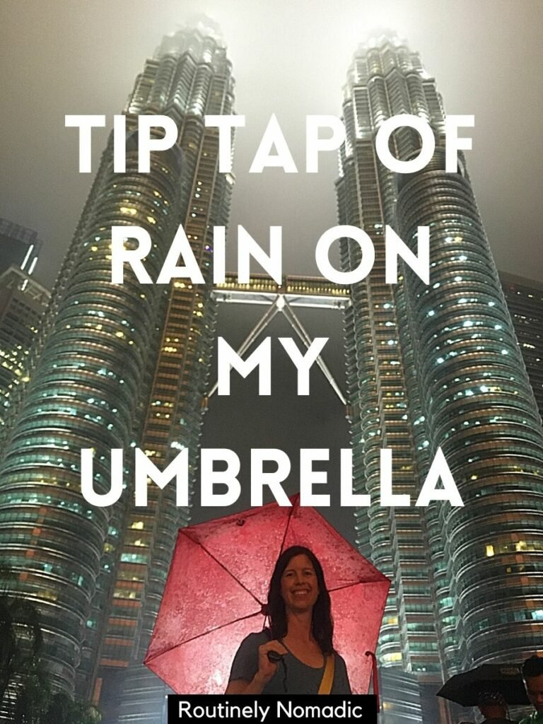 Woman under red umbrella in front of tall towers with a caption for rainy day that says tip tap of rain on my umbrella