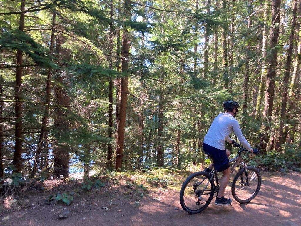 Man on bicycle on path through trees around Cat Lake Squamish