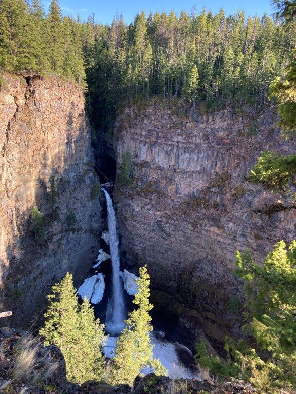 Waterfall coming out of a gap in a tree covered cliff in Clearwater BC Wells Grey Park