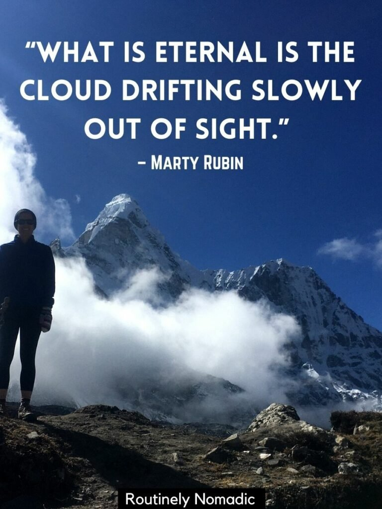 Someone standing in front of low clouds and high mountains with a cloud quotes by marty rubin