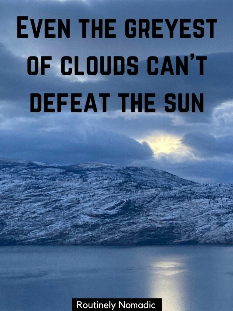 Dark grey clouds with the sun peaking through over a lake with a cloudy captions that reads even the greyest of clouds can't defeat the sun