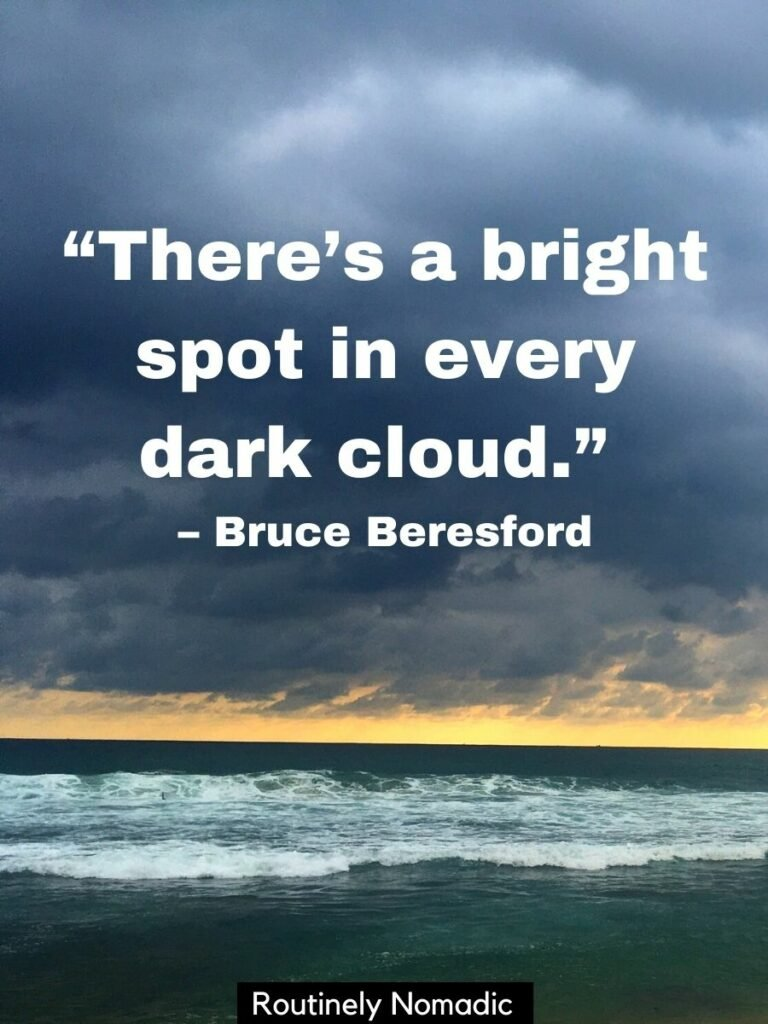 Dark storm clouds over the ocean with a dark cloud quotes that reads there's a bright spot in every dark cloud