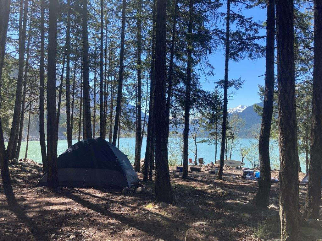 Tent in the trees in front of a blue lake at the Driftwood Campground at Lillooet Lake BC