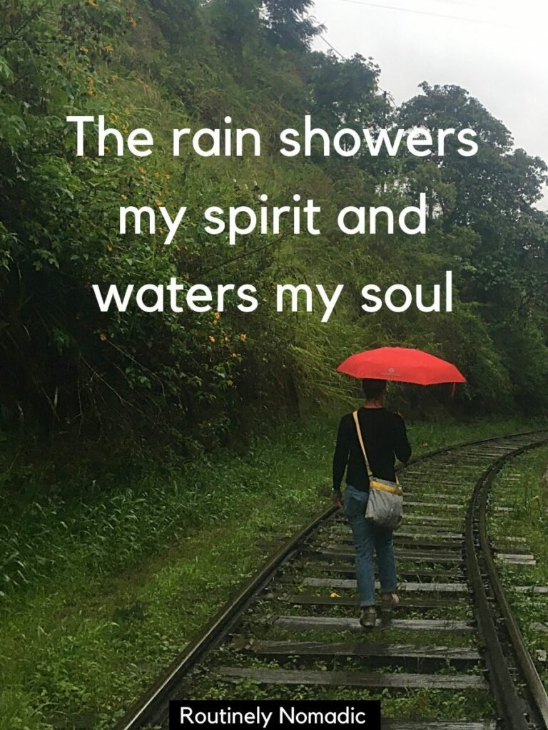 Woman walking on train tracks with an umbrella and a enjoying the rain captions that reads The rain showers my spirit and waters my soul