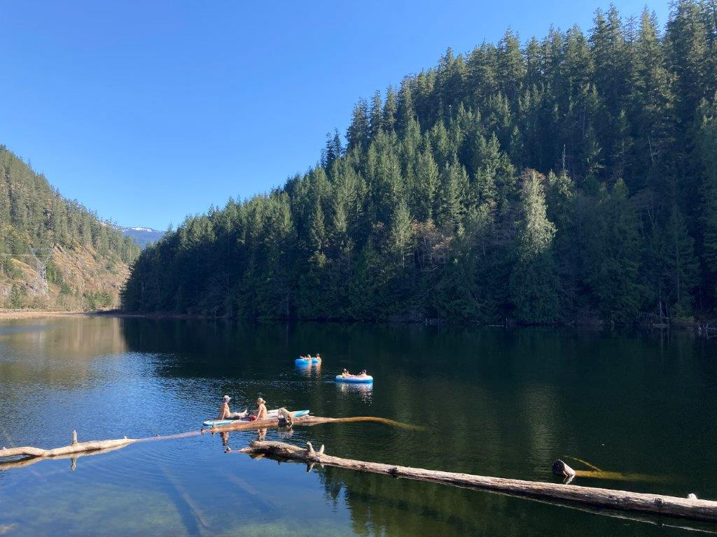 People floating on inflatables and paddleboards and doing some Brohm Lake fishing
