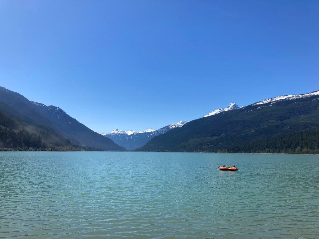 Small inflatable boat on blue lake with snowy mountains behind enjoying Lillooet Lake fishing