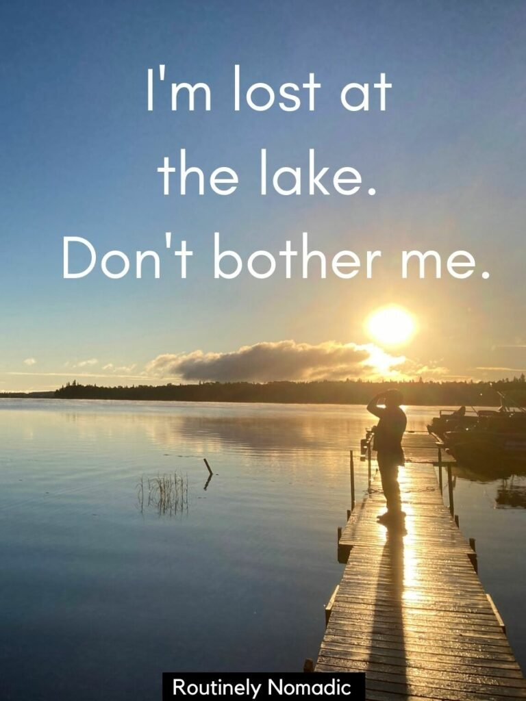 Man standing on dock at sunrise looking at lake with a funny lake captions that reads I'm lost at the lake. Don't bother me.