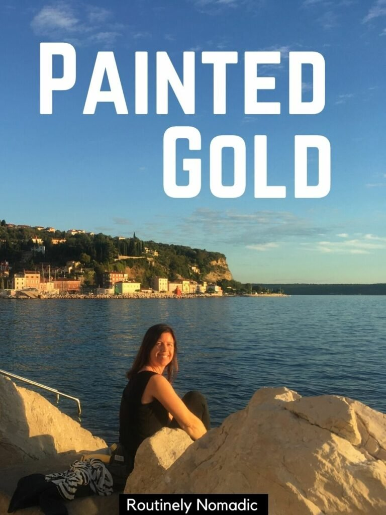 woman sitting on rocks in front of ocean with a golden hour Instagram captions that reads painted gold