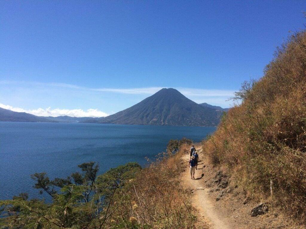 Hikers on trail around Lake Atitlan walking toward a volcano