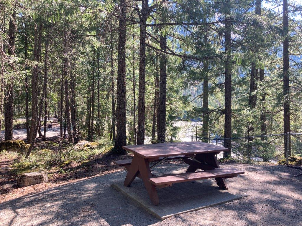 Campsite with picnic table surrounded by trees at the Nairn Falls Campground a good Pemberton camping option