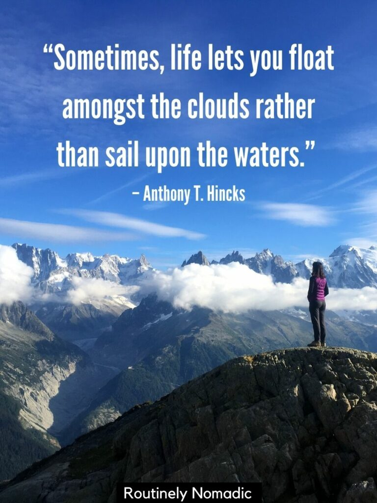 Person standing on rock facing snow covered mountains with a positive cloud quotes by Anthony T. Hincks