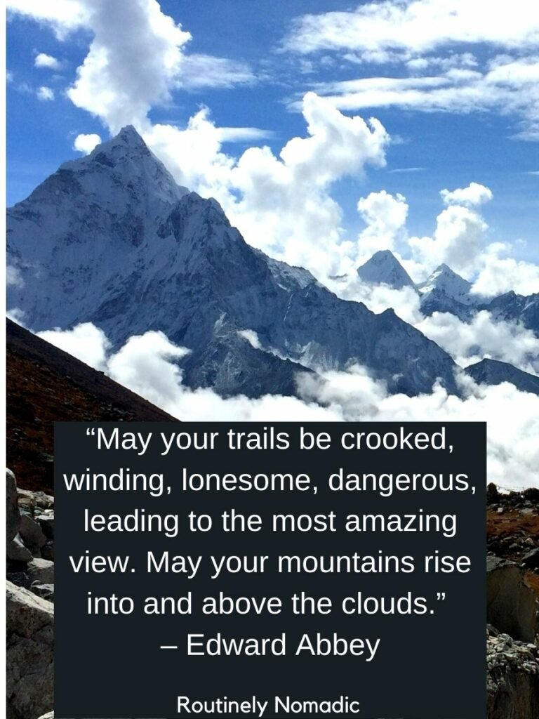 Sharp mountain range above and below the cloud line with a quotes about sky and clouds by Edward Abbey on top