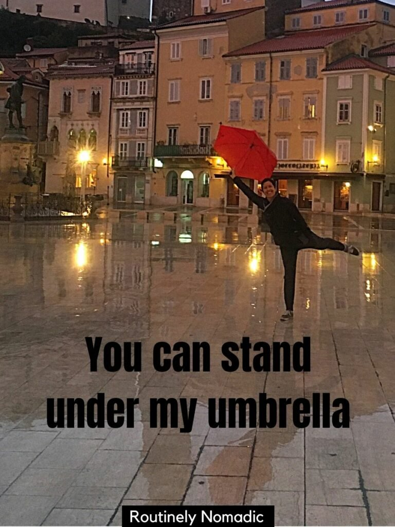 Woman holding umbrella in town square with a rain captions for Instagram that says you can stand under my umbrella