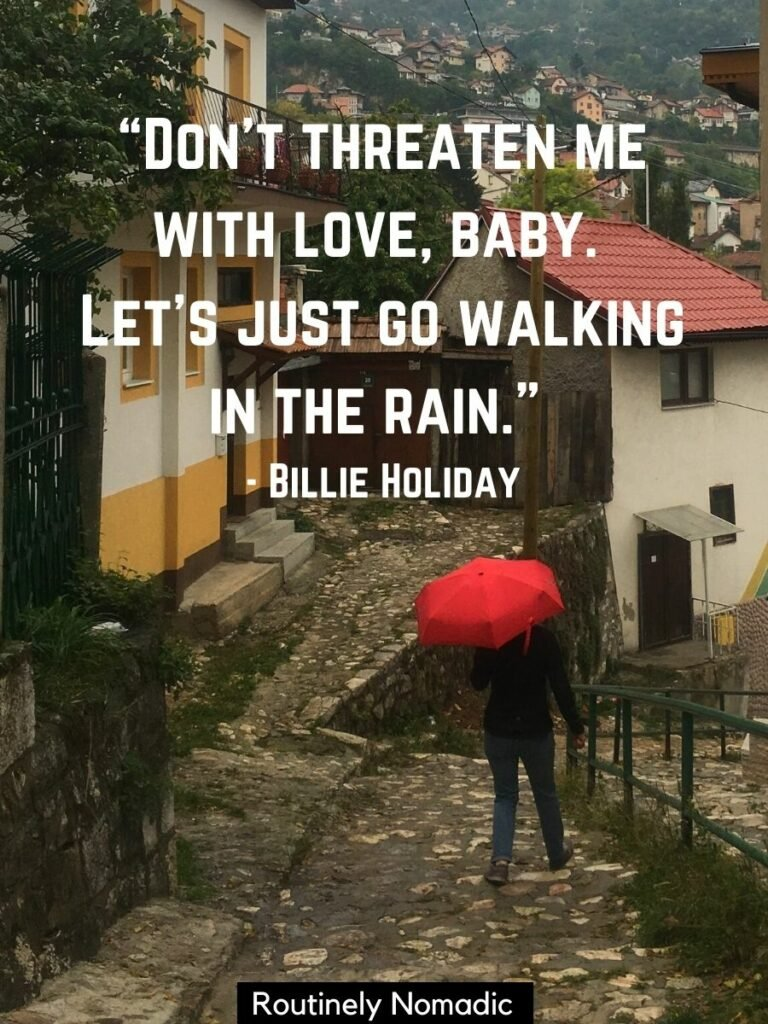Woman with red umbrella walking down cobblestone street with a rain love quotes on top