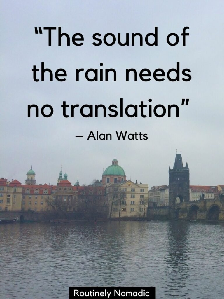 A rainy day with a river and old buildings in Prague with a rain quotes for Instagram that says the sound of rain needs no translation by Alan Watts