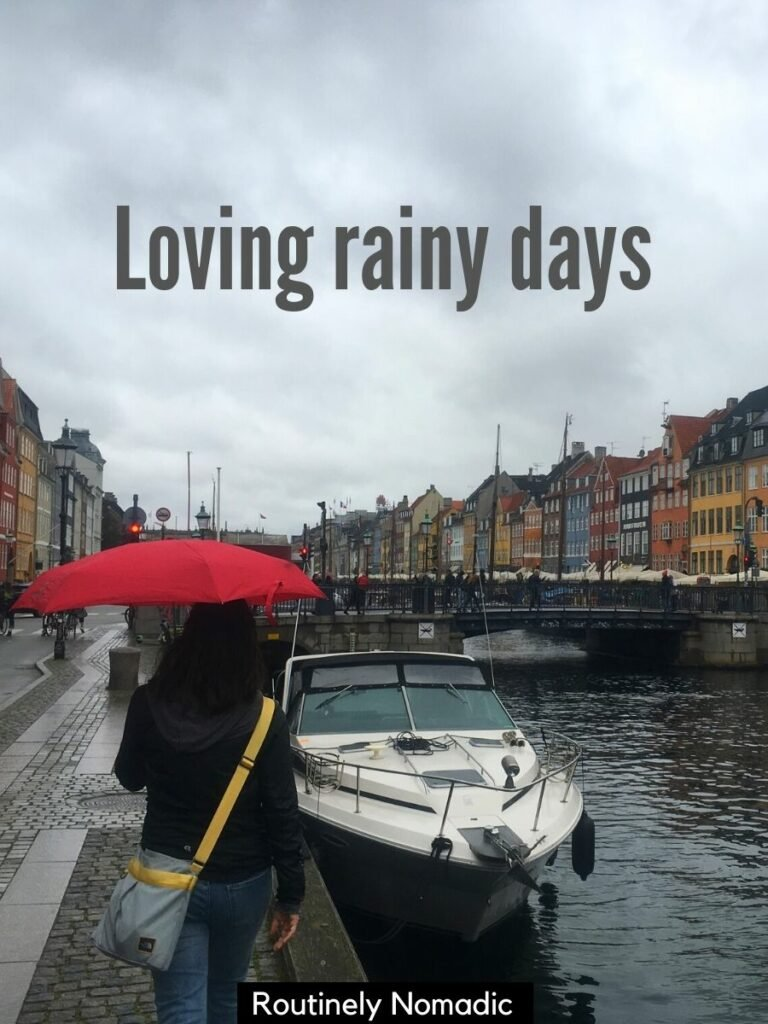 Woman walking under a red umbrella with a rainy day captions that reads loving rainy days