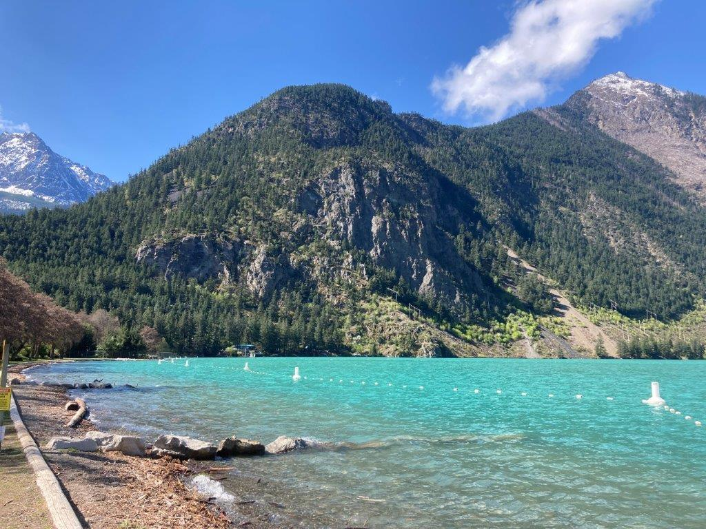 Mountains and blue glacier water with a swimming area at Seton Lake recreation area