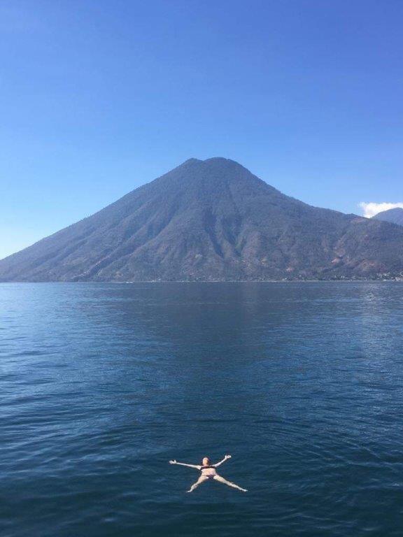 person swimming in Lake Atitlan in front of San Pedro Volcano