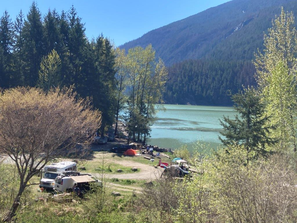 Tents and vans at the Twin One Campground with Lillooet Lake in the background
