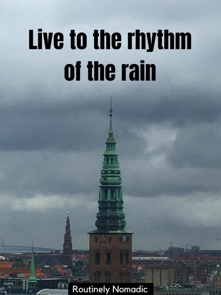 Spire of a church against a cloudy sky with rain captions that says live to the rhythm of the rain
