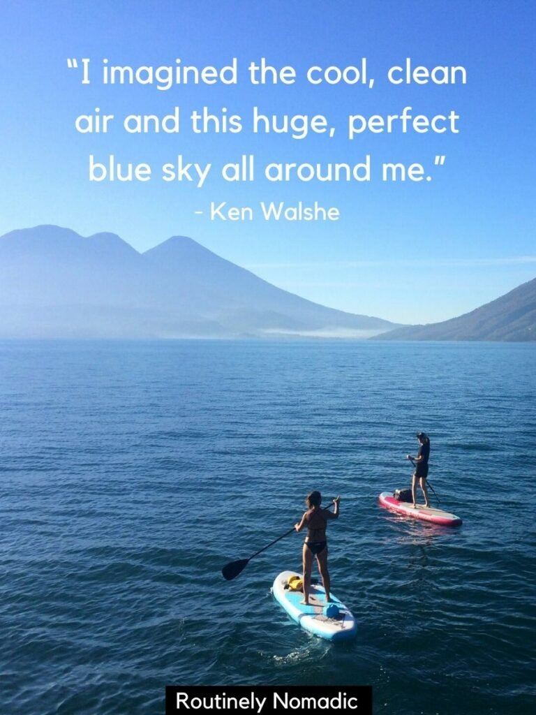 Two people paddleboarding on lake with volcanoes behind and a blue sky quotes by Ken Walshe