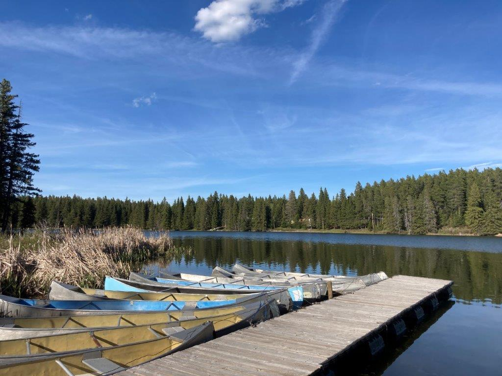 Dock with canoes lined up at Cypress Hills Saskatchewan lake