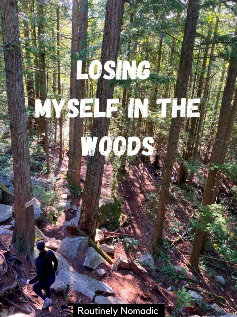 Woman hiking through tall trees with a forest captions that reads losing myself in the woods