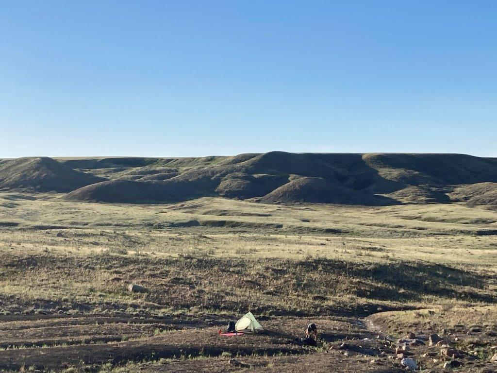 A small tent in the backcountry of the Grasslands National Park with hills behind and blue sky