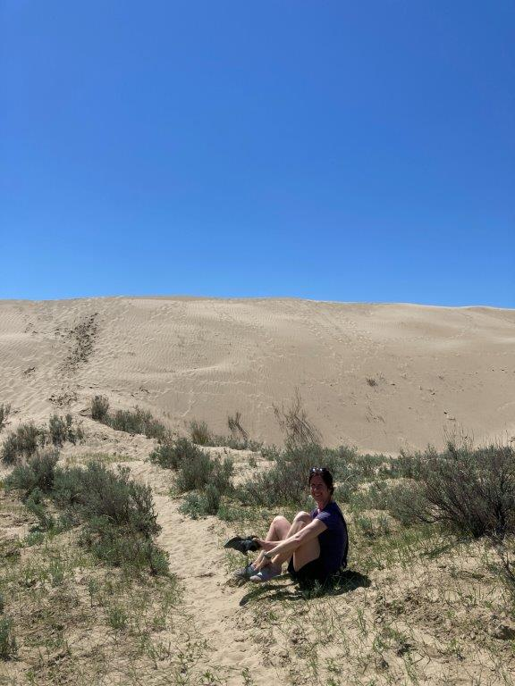 Person emptying out sand from shoes at the great sand hills Saskatchewan