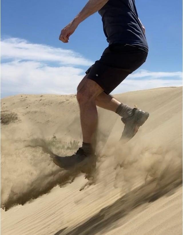 Person running down sand dune at the great sandhills Saskatchewan