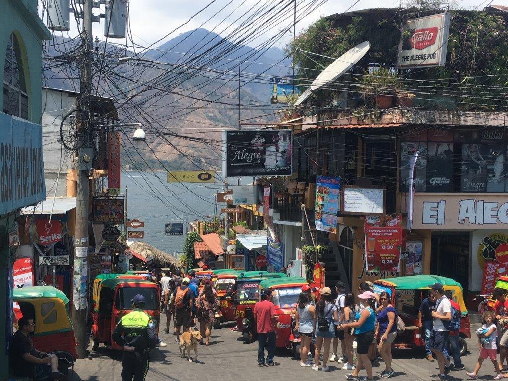 Crowds of tuk tuks and people at main junction up from the dock at San Pedro Lake Atitlan